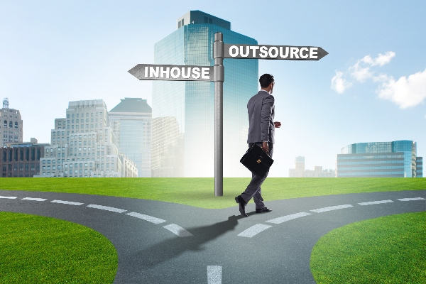 A man walks on a road that splits between one side leading to inhouse solutions and the other to outsourced solutions. He is headed toward outsourcing.