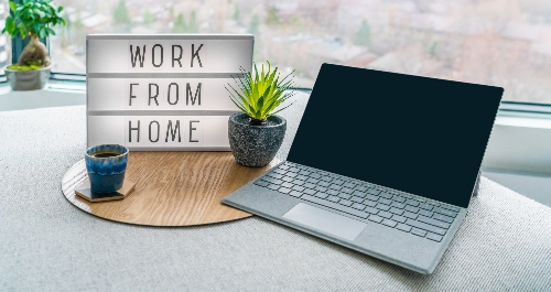 "A laptop sits on a table next to a mug of coffee, a houseplant, and a sign that reads ""work from home."""
